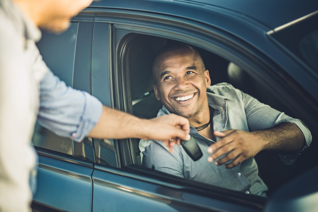 Happy African American businessman taking car keys from a sales person.